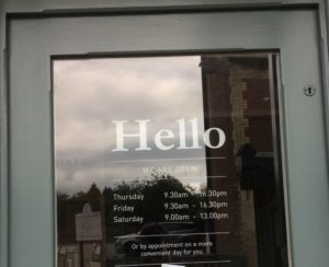 Image of a door with word Hello and opening times